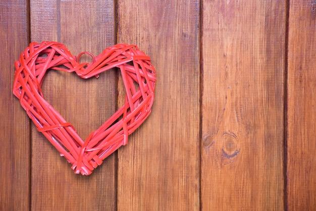 Een gestileerd rood hart gemaakt van een rieten natuurlijk materiaal op een achtergrond van een houten bruin bord. aan de rechterkant is er een plaats voor een inscriptie.