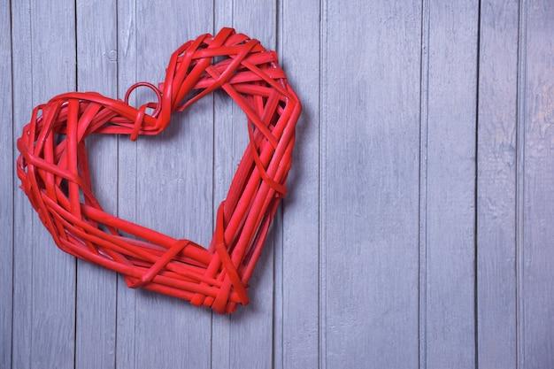 Een gestileerd rood hart gemaakt van een rieten natuurlijk materiaal op een achtergrond van een houten grijs bord. aan de rechterkant is er een plaats voor een inscriptie.