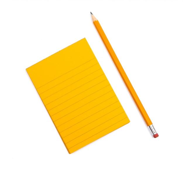 Een gestreept notitieboekje met oranje bladen waarna een gescherpt potlood op witte achtergrond ligt. bespotten met kopie ruimte voor tekst