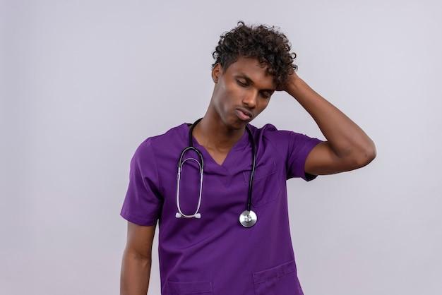 Een gestreste jonge knappe dokter met een donkere huid en krullend haar in violet uniform met een stethoscoop die de hand op het hoofd houdt met gesloten ogen