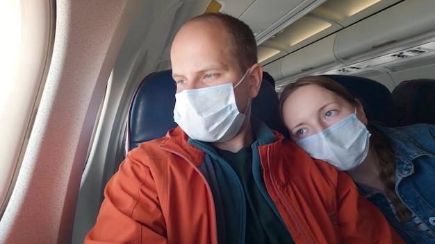 Een getrouwd stel met medische maskers in het vliegtuig. een man en een vrouw kijken uit het vliegtuigraam. mensen reizen om zich te beschermen tegen het coronavirus. 4k uhd