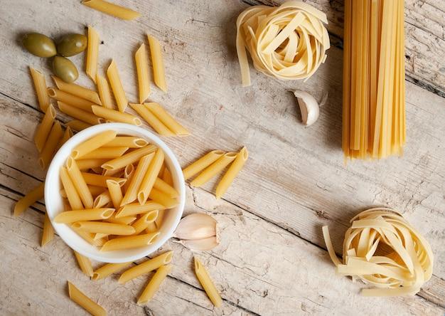 Een gevarieerd assortiment pasta op een houten ondergrond met knoflook en groene olijven. foto van bovenaf genomen.