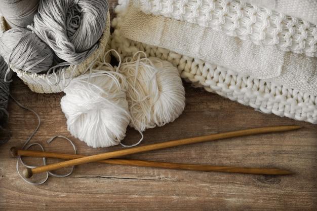 Een gevlochten mand met wit en grijs draad voor brei- en breinaalden. witte truien en garen voor het breien van close-up. winter