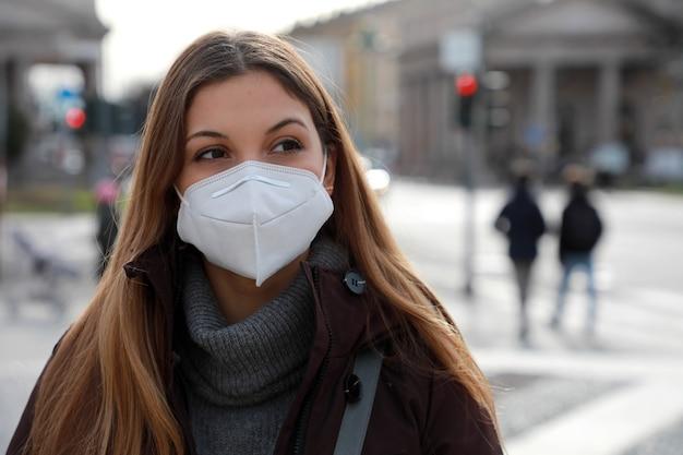 Een gevoel van verbijstering. sluit omhoog van jonge vrouw die in de winterkleren in straat loopt die beschermend masker ffp2 kn95 draagt. meisje met gezichtsmasker voelt zich alleen tijdens een pandemie.