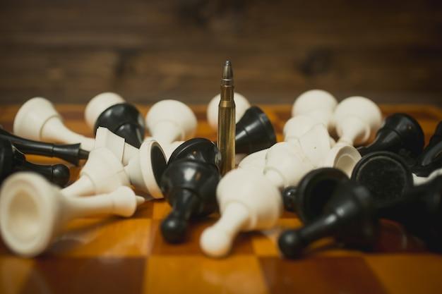 Een geweerkogel op schaakbord tussen liggende schaakstukken
