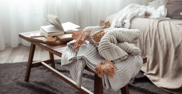 Een gezellige huiscompositie met een gebreide trui, een boek en bladeren in het interieur van de kamer.