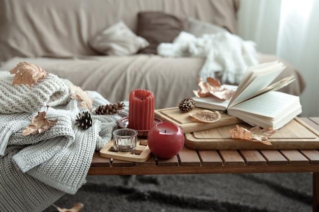 Een gezellige huiscompositie met kaarsen, een boek, gebreide truien en bladeren in het interieur van de kamer.