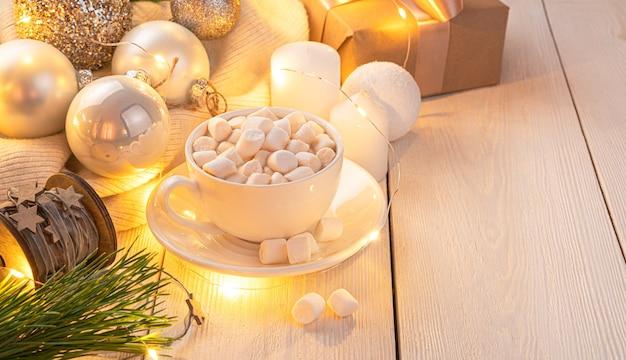 Een gezellige kerstcompositie met een kopje koffie en kerstboomspeelgoed verlicht door een slinger. het concept van kerstmis en nieuwjaar.