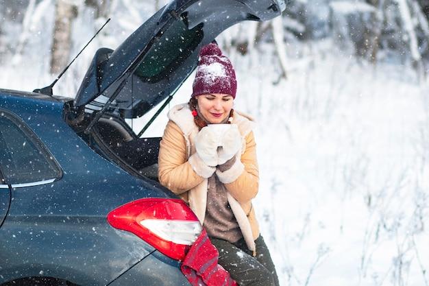 Een gezellige vrouw, een vrouw in warme winterkleren, drinkt een warme drank, thee of koffie, zit in de kofferbak van een auto en glimlacht. vakantie, reizen met de auto, sneeuwkou.
