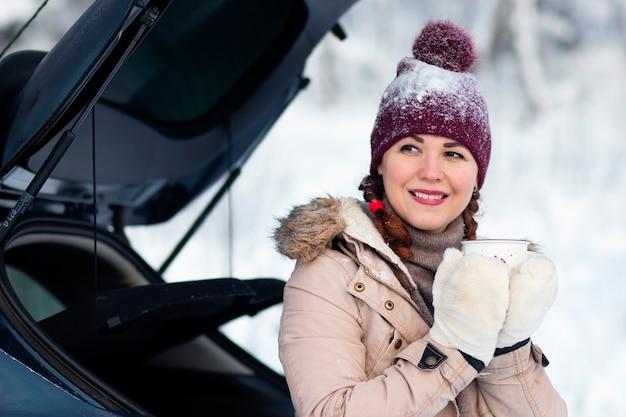 Een gezellige vrouw lacht, een vrouw in warme winterkleren houdt een mok vast, zit in de kofferbak van een auto en lacht. vakantie, reizen met de auto, sneeuwkou.