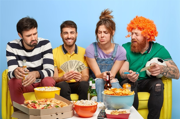Een gezelschap van vrienden kijkt voetbal op tv, een man maakt een weddenschap voor het winnen van zijn favoriete team