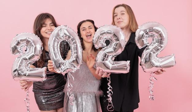 Een gezelschap van vrolijke vriendinnen op een roze achtergrond met zilveren ballonnen in de vorm van de cijfers 2022.