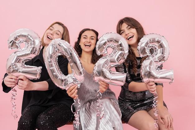 Een gezelschap van vrolijke vriendinnen op een roze achtergrond met zilveren folieballonnen in de vorm van de cijfers 2022, die het nieuwe jaar viert.