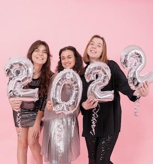 Een gezelschap van vrolijke vriendinnen op een roze studioachtergrond met zilveren ballonnen in de vorm van de nummers 2022.