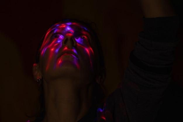 Een gezicht in het donker bedekt met felgekleurde vlekken van een felle lamp gekleurde schittering van de lamp
