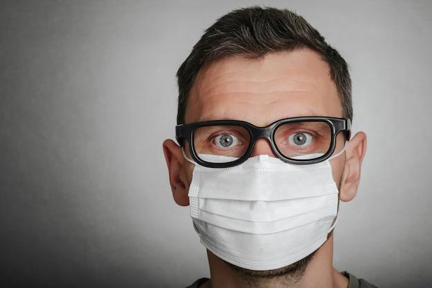 Een gezicht van een masker-dragende man met angst in het oog