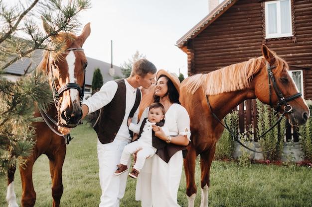 Een gezin in witte kleren met hun zoon staat in de buurt van twee prachtige paarden in de natuur. een stijlvol stel met een kind wordt gefotografeerd met paarden