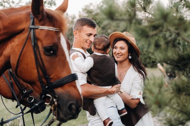 Een gezin in witte kleren met hun zoon staat naast twee prachtige paarden in de natuur. een stijlvol stel met een kind en paarden.