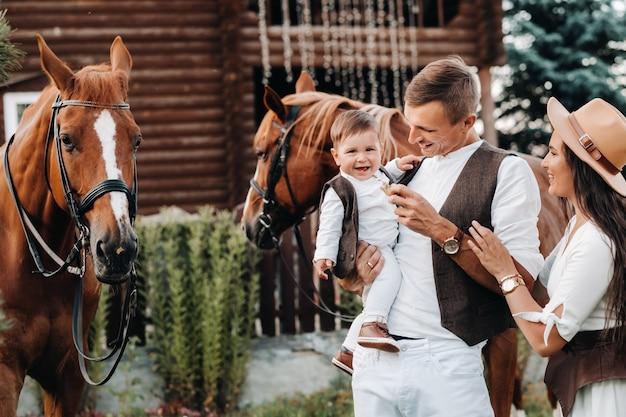 Een gezin in witte kleren met hun zoon staat naast twee prachtige paarden in de natuur. een stijlvol stel met een kind wordt gefotografeerd met paarden.