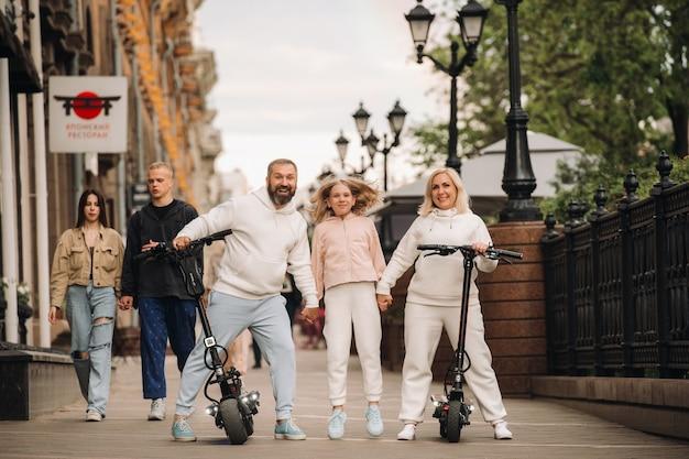 Een gezin in witte kleren staat in de stad op elektrische scooters.