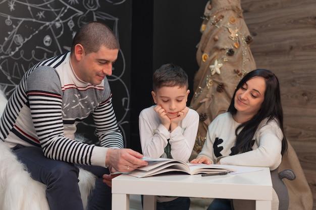 Een gezin leest samen met een kind een boek tegen de achtergrond van nieuwjaarsversieringen