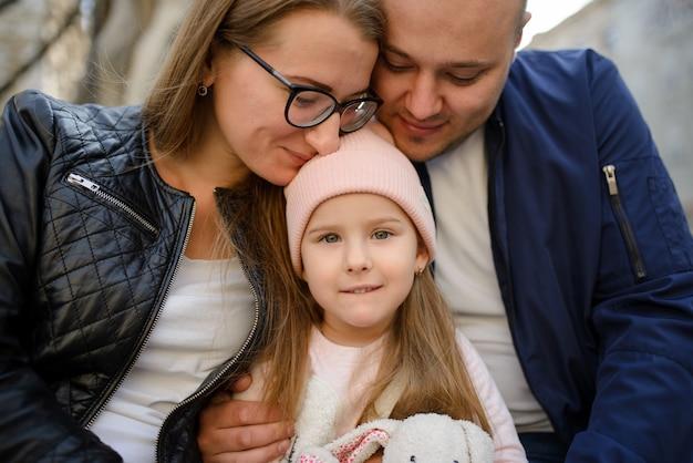 Een gezin met één dochter knuffelt en heeft samen plezier. Premium Foto