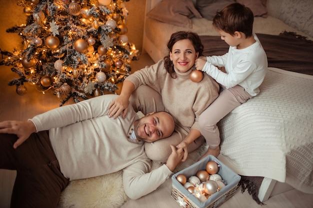 Een gezin met een kind thuis in de slaapkamer bij het bed bij de kerstboom.
