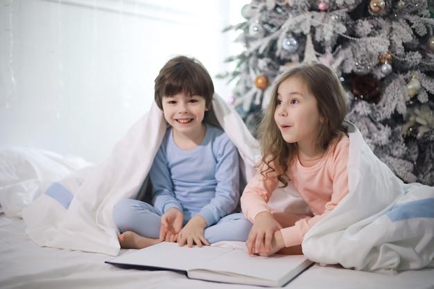 Een gezin met kinderen die zich tijdens de kerstvakantie op het bed onder de dekens vermaken.