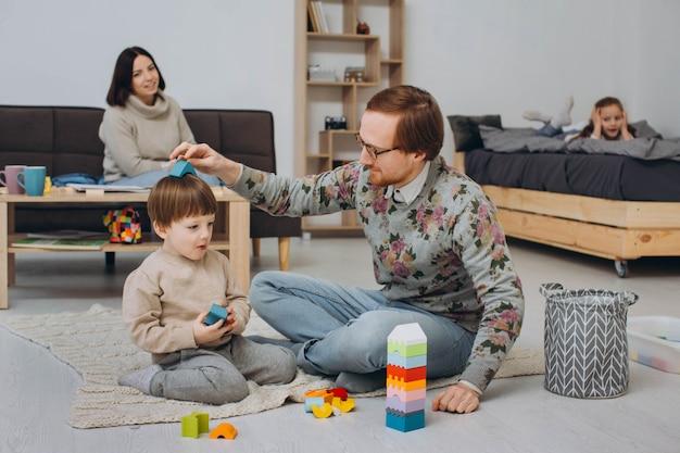 Een gezin met twee kinderen die samen op de vloer spelen en thuis plezier hebben.