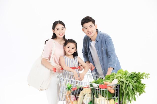 Een gezin van drie koopt groenten in de supermarkt