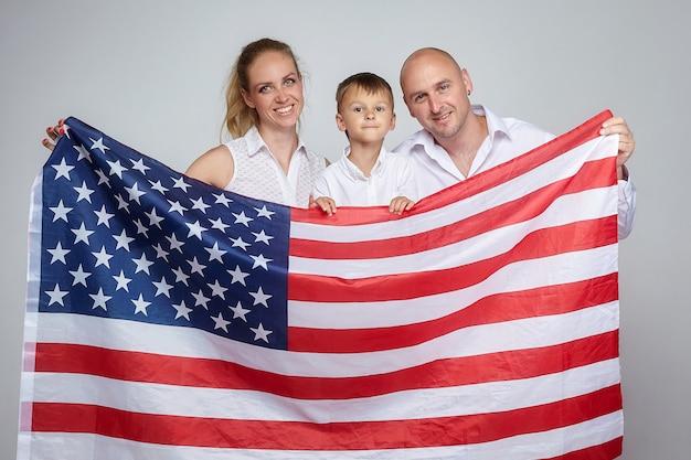 Een gezin van drie met een amerikaanse vlag op een witte achtergrond