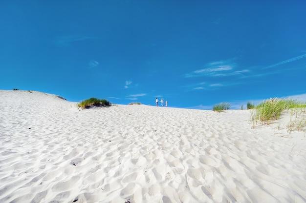 Een gezin van drie wandelingen in de zandduinen bij de stad nida, litouwen.