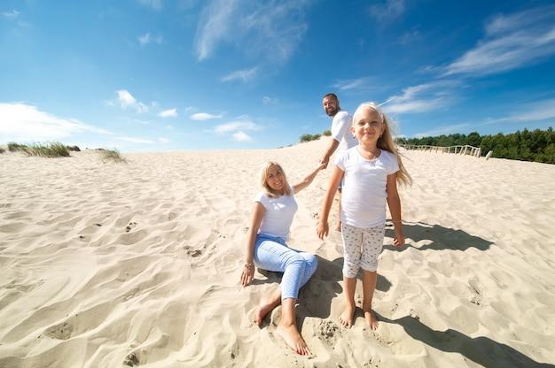 Een gezin van drie zit op de zandduinen bij de stad nida, litouwen