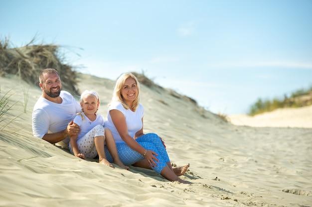 Een gezin van drie zit op de zandduinen bij de stad nida, litouwen.