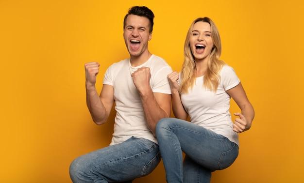 Een gezin van twee poseert op een gele achtergrond, draagt vrijetijdskleding en drukt geluk en overwinning uit met hun poses en gebaren.