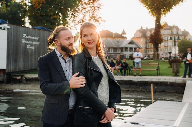 Een gezin van twee staat bij zonsondergang op een pier in de oude binnenstad van oostenrijk. een man en een vrouw omhelzen elkaar aan de dijk van een kleine stad in oostenrijk.