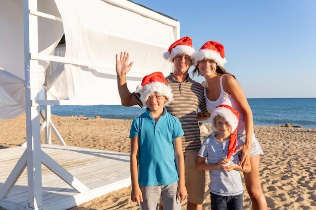 Een gezin van vier, moeder, vader en twee kinderen in kerstman hoeden in zandstrand aan zee. gelukkig kerstfeest familie vieren het nieuwe jaar aan de kust.
