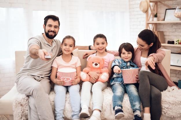 Een gezin van vijf zit op de bank in hun appartement.