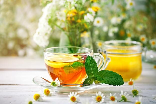 Een gezond kopje thee, een pot honing en bloemen. selectieve aandacht.
