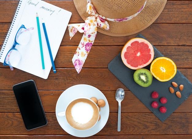 Een gezond vertrek voor een dag in goede conditie. rustieke houten tafel met een warme cappuccino en wat citrusvruchten, drie kleine frambozen en amandelen.