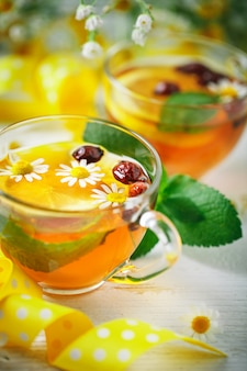 Een gezonde kop thee met citroen, rozenbottel, munt en bloemen. selectieve aandacht.
