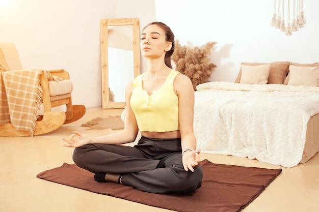Een gezonde leefstijl. een vrouw doet yoga, zit in een lotushouding. thuisquarantaine, mat, oefenen