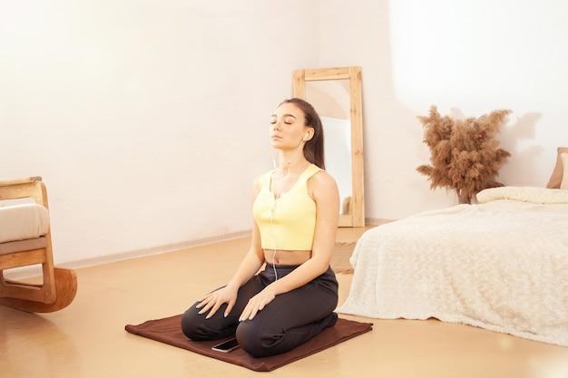 Een gezonde leefstijl. een vrouw oefent en luistert naar muziek. zittend op een fitnessmat. yoga