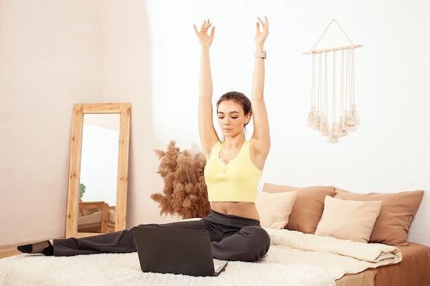 Een gezonde leefstijl. een vrouw op het bed. online ochtendtraining met een laptop.