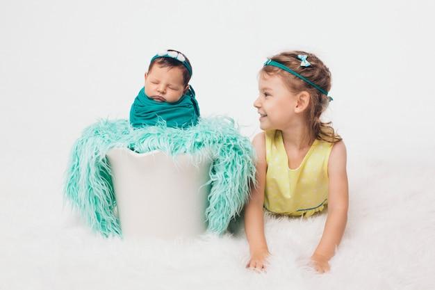 Een gezonde levensstijl, de bescherming van kinderen, winkelen - een tiener met een pasgeboren baby die samen speelt. gelukkige jonge geitjes: broer en zus op witte achtergrond