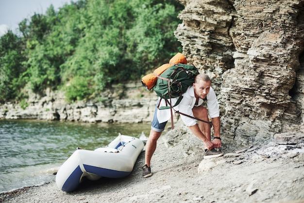 Een gezonde man bereidt zich voor op het beklimmen van een heuvel en nieuwe avonturen na een lange reis in de boot.
