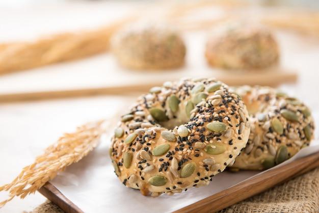 Een gezonde meergranen donut broodjes op een houten plaat in een bakkerij