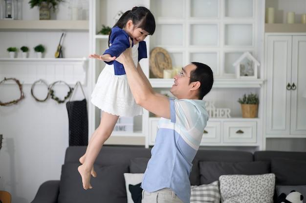Een gezonde vader houdt gelukkige schattige dochter vliegen en vliegtuig spelen samen thuis in het weekend, familie concept.