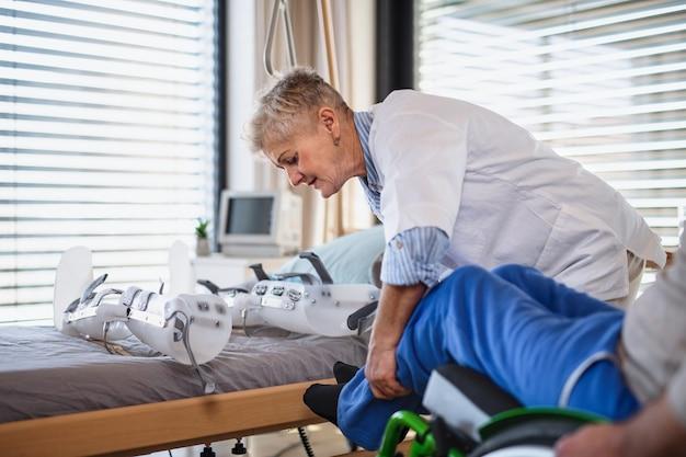 Een gezondheidswerker en een man verlamde senior patiënt in het ziekenhuis, die orthese aanbracht.
