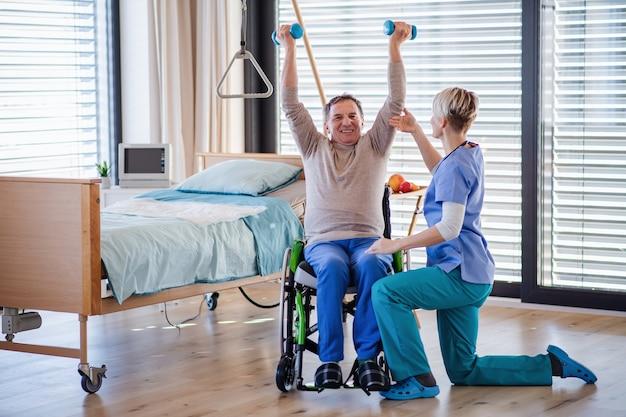 Een gezondheidswerker en senior patiënt in het ziekenhuis, fysiotherapie concept.